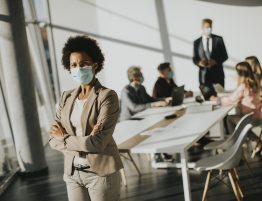 Woman with Mask Standing in Conference Room